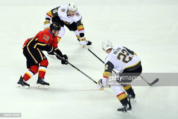 Calgary Flames Left Wing Johnny Gaudreau stickhandles toward Vegas Golden Knights Defenceman Colin Miller and Defenceman Nick Holden during the third...