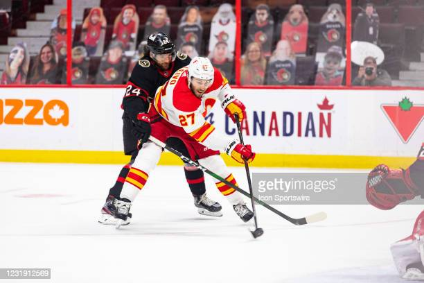 Calgary Flames Right Wing Josh Leivo gets a shot off with Ottawa Senators Defenceman Christian Wolanin all over him during first period National...
