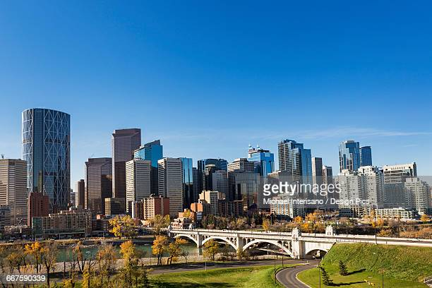 Calgary skyline with bridge spanning across river, autumn coloured trees and blue sky