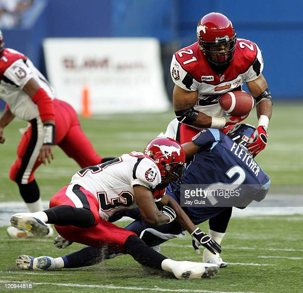 Calgary Stampeders Running Back Joffrey Reynolds nearly fumbles while being tackled by Toronto's Michael Fletcher at Rogers Centre in Toronto, Canada...