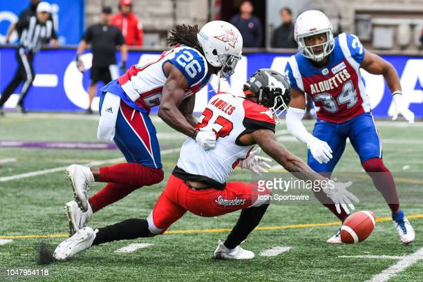 Calgary Stampeders Wide receiver Markeith Ambles drops the ball after a tackle from Montreal Alouettes Defensive back Tevaughn Campbell during the...