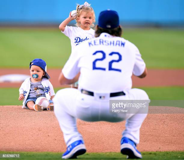 Cali Ann Kershaw throws throws out a ceremonial first pitch to her dad Clayton Kershaw of the Los Angeles Dodgers as brother Charley Kershaw sits on...