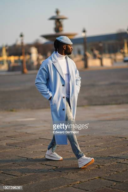 Cali Chiki wears a blue wool beanie hat from Shein, a white turtleneck wool pullover , a blue long wool coat from Boohoo, ripped jeans, white...