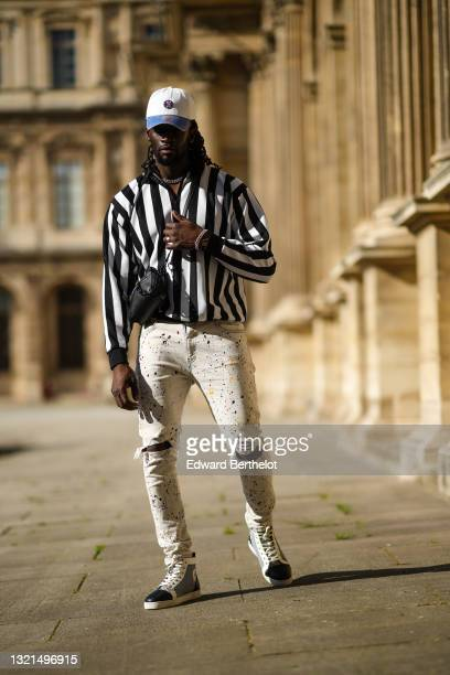 Cali Chiki wears a white and blue denim jean Mitchell & Ness cap, a black and white striped zipped polo shirt, white with multicolor paint spots...
