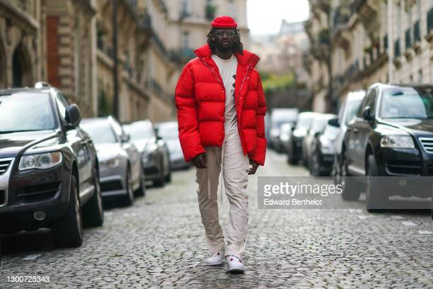 Cali Chiki wears glasses, a red wool beanie hat, a beige t-shirt from Asos, a red large winter puffer coat/jacket from MNML.LA , beige pants with...