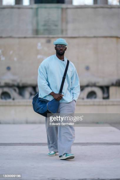 Cali Chiki wears glasses from Ray-Ban, a pale blue wool beanie hat from HM, a pale blue oversized pullover from Asos, gray jogger sport pants from...