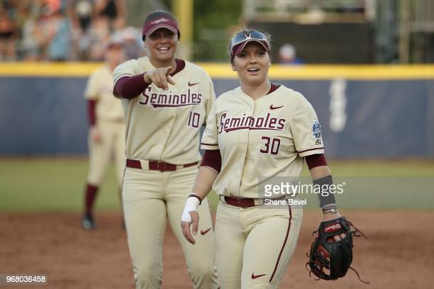 Cali Harrod and Jessie Warren of the Florida State Seminoles share a laugh against the Washington Huskies during the Division I Women's Softball...