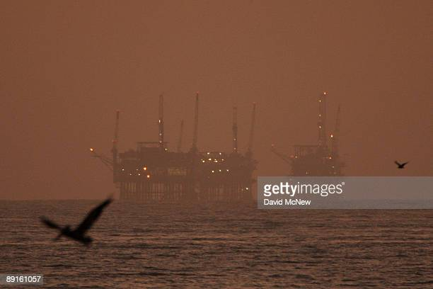 California brown pelicans fly near offshore oil rigs after sunset on July 21 2009 near Santa Barbara California After months of partisan bickering...
