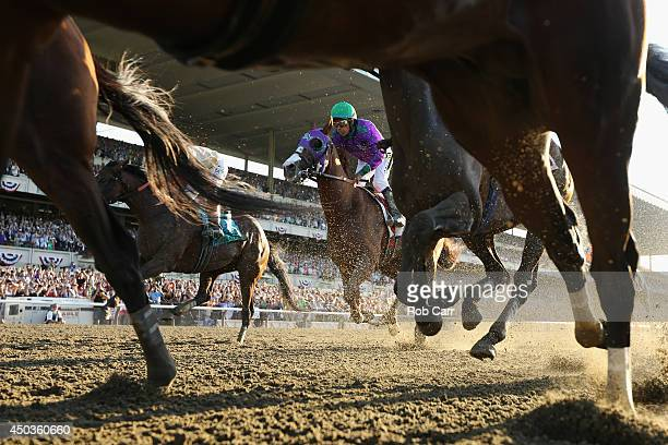 California Chrome ridden by Victor Espinoza crosses the finish line tied for fourth during the 146th running of the Belmont Stakes at Belmont Park on...