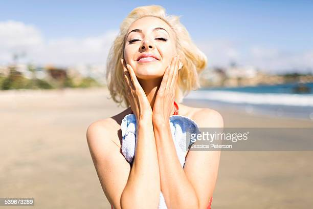USA, California, Costa Mesa, Portrait of blond woman on beach applying sun screen