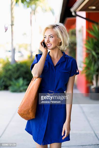 usa, california, costa mesa, woman in blue dress outside building using phone - one mid adult woman only stock pictures, royalty-free photos & images