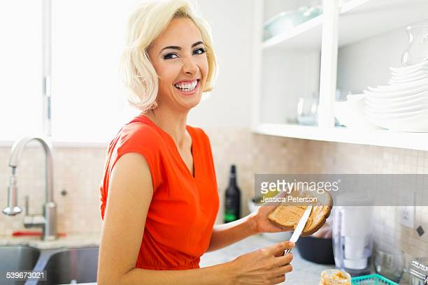 USA, California, Costa Mesa, Woman making toast with peanut butter in kitchen and smiling to camera
