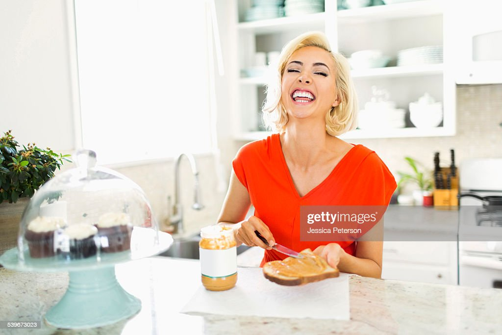 USA, California, Costa Mesa, Woman making toast with peanut butter in kitchen and laughing : Stock Photo