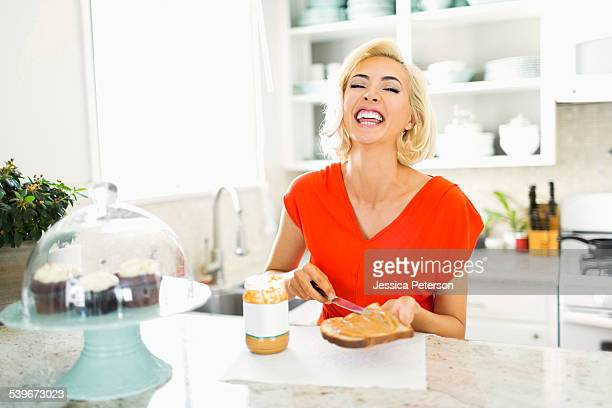USA, California, Costa Mesa, Woman making toast with peanut butter in kitchen and laughing