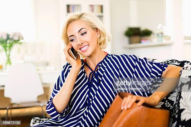 usa, california, costa mesa, woman using phone in living room - コスタメサ ストックフォトと画像