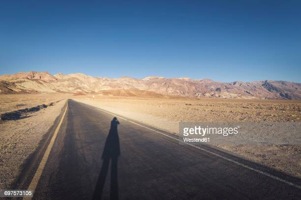 USA, California, Death Valley, Artists Drive with womans shadow at sunset