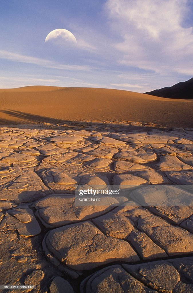 USA, California, Death Valley, cracked soil in desert with moon : Stockfoto