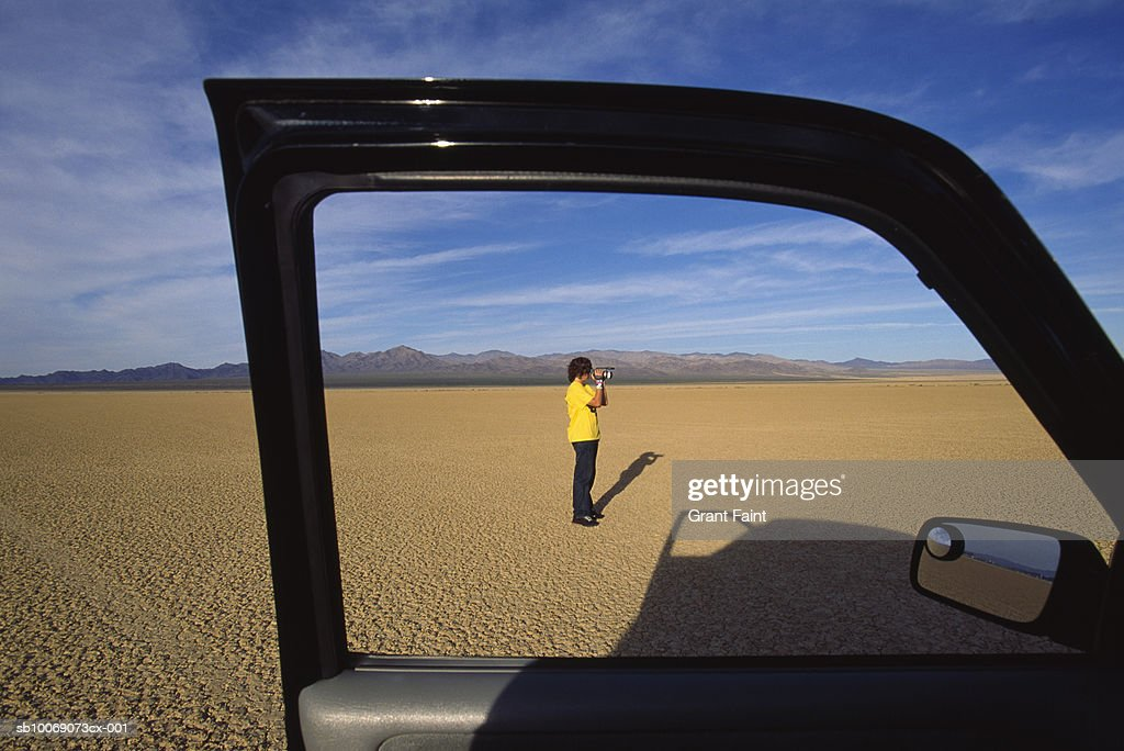 USA, California, Death Valley, teenage boy (14-15) filming desert near car : Stockfoto