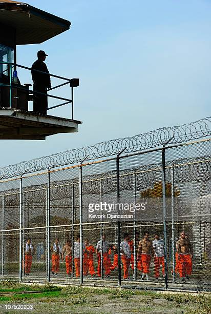 California Department of Corrections officer looks on as inmates at Chino State Prison exercise in the yard December 10 2010 in Chino California The...