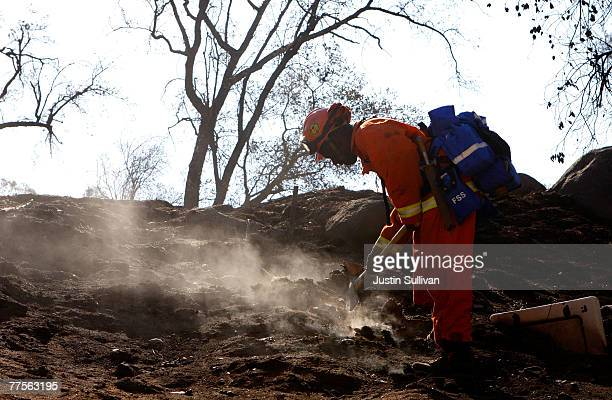 California Department of Corrections prison inmate firefighter mops up a hot spot near a destroyed home October 30 2007 in Ramona California Clean up...