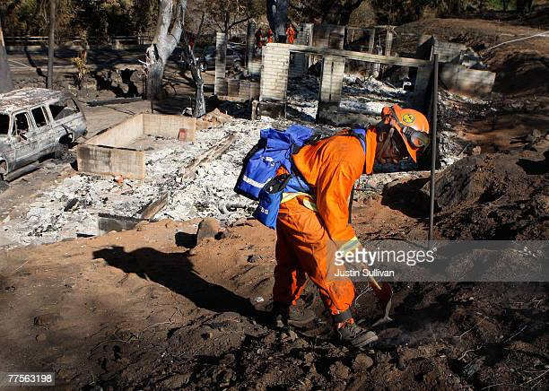 California Department of Corrections prison inmate firefighter mops up a hot spot at a destroyed home October 30 2007 in Ramona California Clean up...