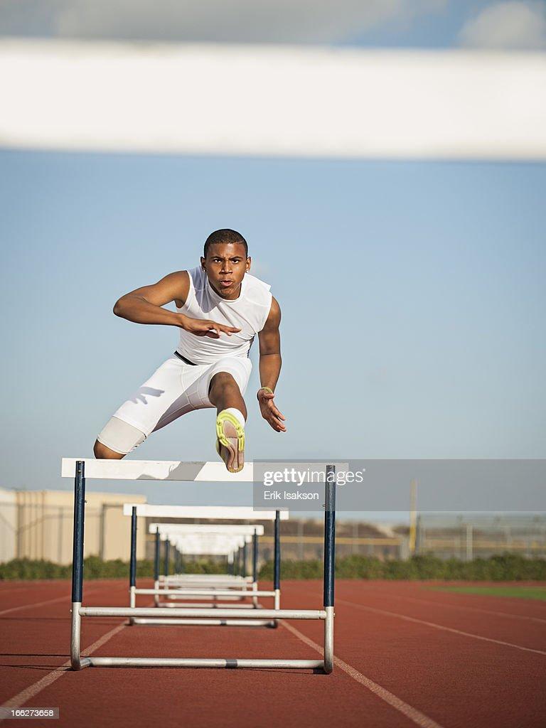 USA, California, Fontana, Boy (12-13) hurdling on running track : Stock Photo