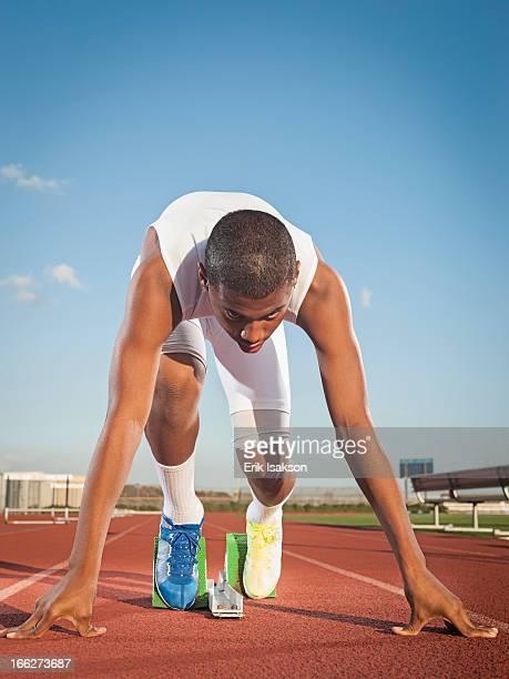 USA, California, Fontana, Boy (12-13) preparing for running on starting line