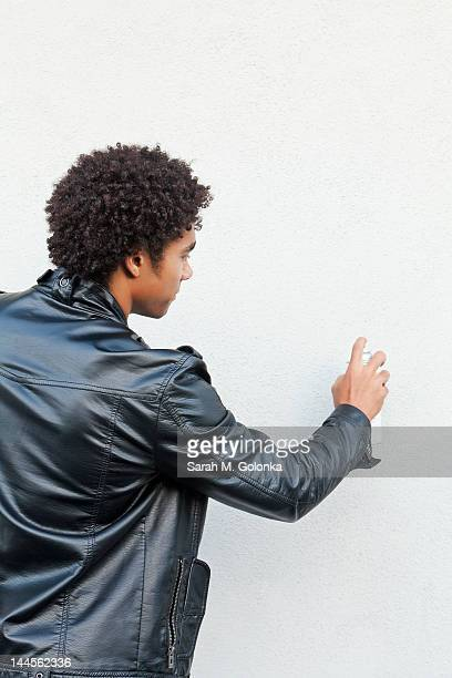USA, California, Gardena, Man holding spray paint against white wall, studio shot