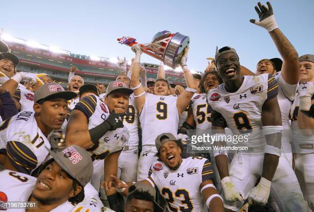 California Golden Bears players celebrate with the trophy after defeating the Illinois Fighting Illini 35-20 in the RedBox Bowl at Levi's Stadium on...