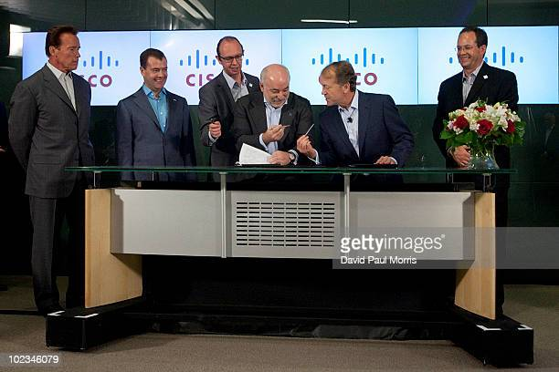 California Gov Arnold Schwarzenegger and Russian President Dmitry Medvedev watch as President of Renova Group Viktor Vekselberg and Cisco Chairman...
