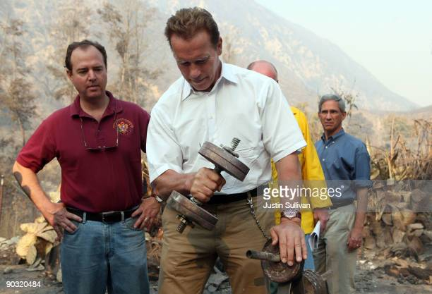 California Gov Arnold Schwarzenegger lifts a charred dumbbell as US Rep Adam Schiff and California State Insurance Commissioner Steve Poizner look on...