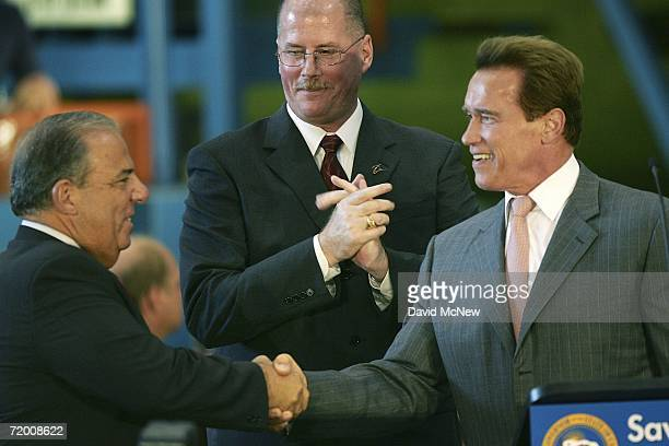 California Gov Arnold Schwarzenegger shakes hands with Long Beach Mayor Bob Foster as Dave Bowman vice president and C17 program manager for Boeing...