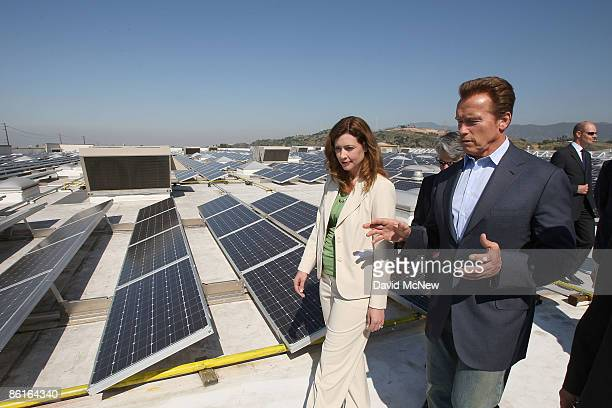 California Gov Arnold Schwarzenegger tours a solar panel installation on the roof of a Sam's Club store with WalMart vice president and California...