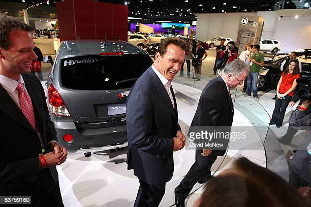 California Gov Arnold Schwarzenegger walks by a Saturn VUE Green Line hybrid vehicle as the Los Angeles Auto Show opens for press previews at the Los...