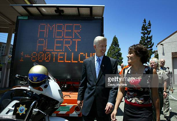 California Gov Gray Davis and 18yearold Jacqueline Marris pass an electronic freeway alert sign as they arrive to the commemoration of the first year...