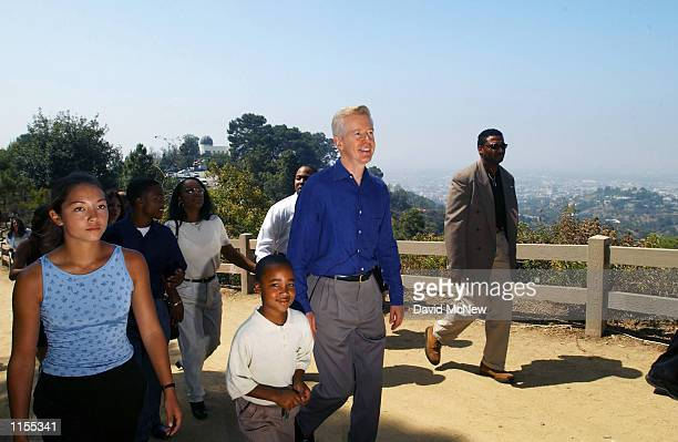 California Gov Gray Davis walks up a hill with local families in Griffith Park overlooking a hazy Los Angeles skyline to sign Assembly Bill 1493 July...