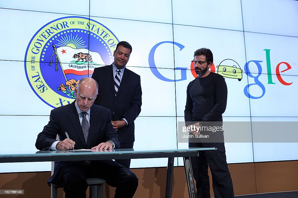 California Gov. Jerry Brown (L) signs State Senate Bill 1298 as California State Sen. Alex Padilla (C) and Google co-founder Sergey Brin (R) look on at the Google headquarters on September 25, 2012 in Mountain View, California. California Gov. Jerry Brown signed State Senate Bill 1298 that allows driverless cars to operate on public roads for testing purposes. The bill also calls for the Department of Motor Vehicles to adopt regulations that govern licensing, bonding, testing and operation of the driverless vehicles before January 2015.