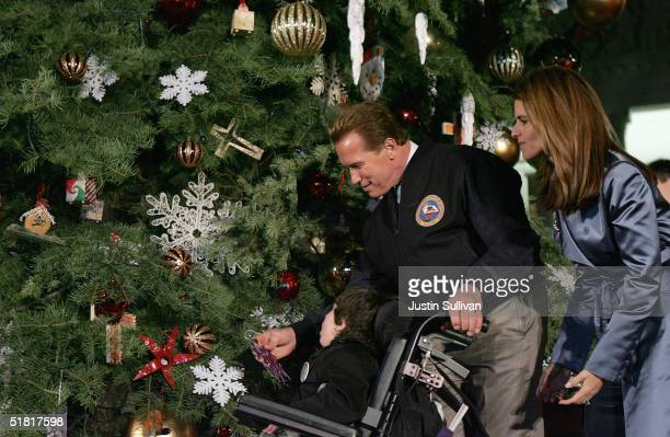 California Governor Arnold Schwarzenegger and his wife Maria Shriver help a handicapped child hang an ornament on the California State Christmas tree...