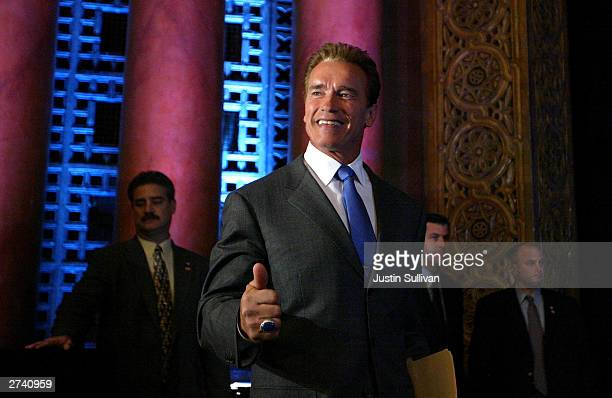 California Governor Arnold Schwarzenegger gives the thumbsup to reporters during his first news conference as governor November 18 2003 in Sacramento...