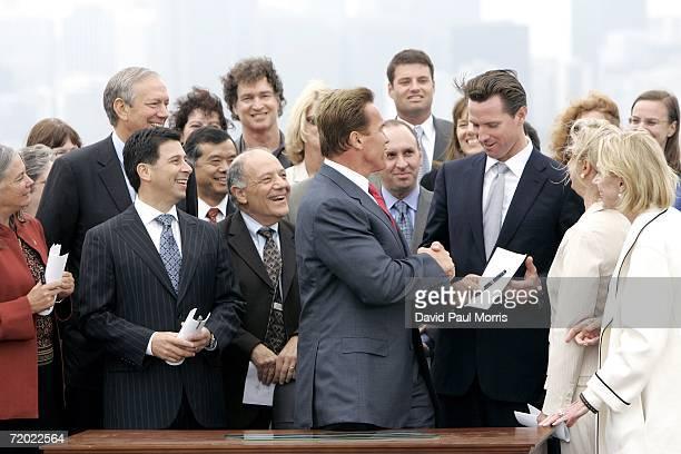 California Governor Arnold Schwarzenegger hands San Francisco Mayor Gavin Newsom a copy of his signed bill AB32 the California Global Warming...
