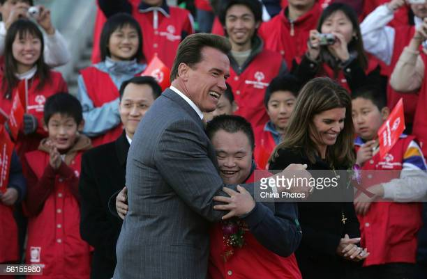 California Governor Arnold Schwarzenegger hugs one of the Special Olympic athletes at a ceremony to celebrate the growth of Special Olympics for...