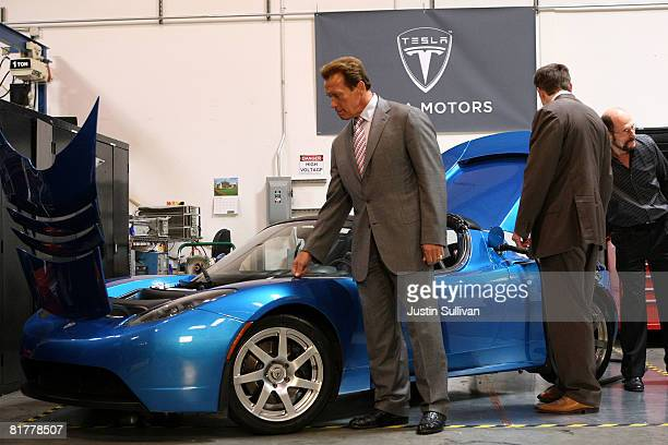 California governor Arnold Schwarzenegger looks at a Tesla Roadster before a news conference June 30 2008 at Tesla Motors in San Carlos California...
