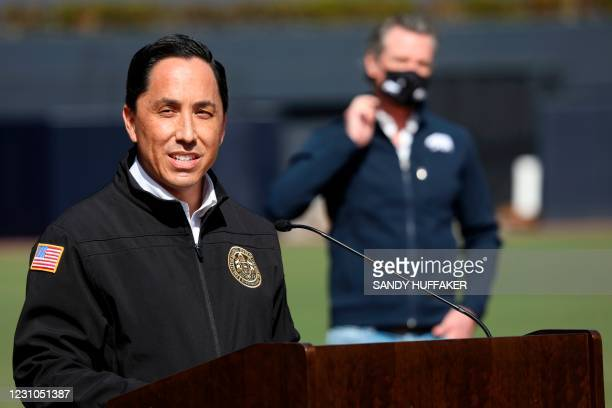 California Governor Gavin Newsom listens as San Diego Mayor Todd Gloria speaks to members of the media during a press conference at Petco Park,...