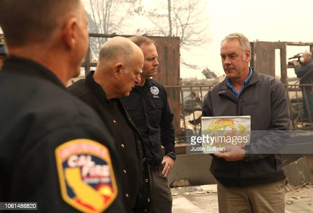 California Governor Jerry Brown and FEMA Adminstrator Brock Long look on as US Secretary of the Interior Ryan Zinke holds up a child's school work as...
