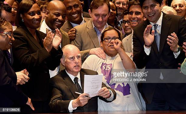 California Governor Jerry Brown displays the bill he just signed that will raise the state's minimum wage to $15 an hour by 2022 while surrounded by...