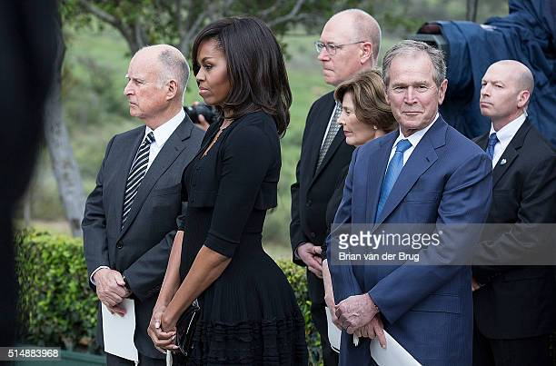 California governor Jerry Brown left first fady Michelle Obama former first lady Laura Bush and former president George W Bush right wait to pay...