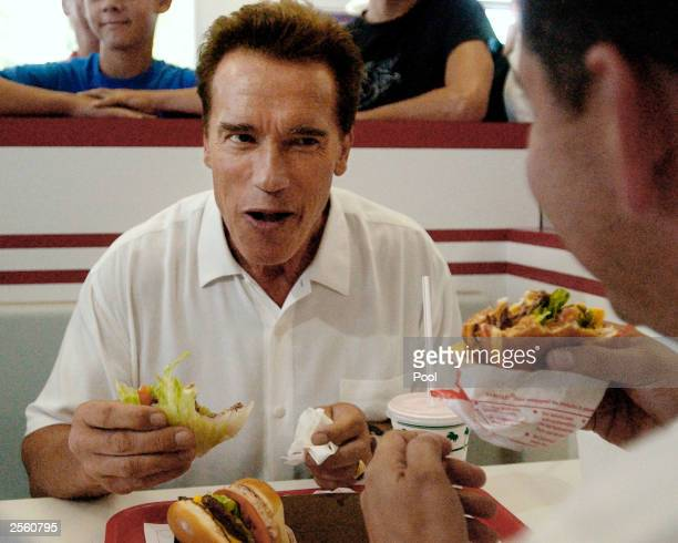 California gubernatorial candidate Arnold Schwarzenegger eats at an IN Out restaurant with with California Assemblyman Abe Maldonado during a lunch...