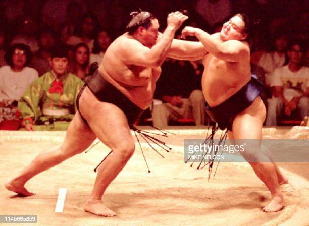 Hawaiiborn sumo grand champion Akebono pushes his Japanese opponent Daisyoho out of the ring 05 June during second round sumo action in the San Jose...