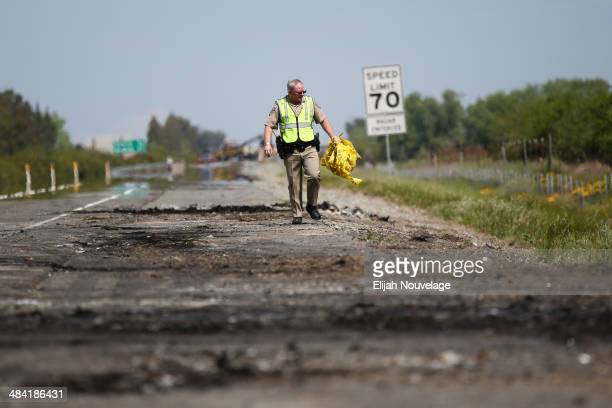California Highway Patrol officer Joe Stokes clears away crime scene tape at the scene of a deadly crash on April 11 2014 in Orland California Ten...