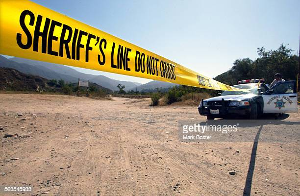 ––A California Highway Patrol officer mans the roadblock on Trabuco Canyon Road near the site of where a partially clad woman was found badly beaten...